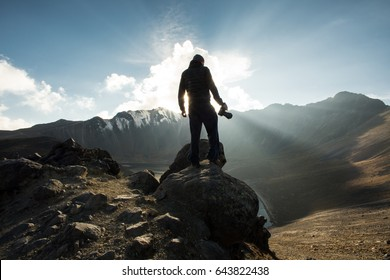 PHOTOGRAPHER SILHOUETTE AT MOUNTAIN TOP LANDSCAPE