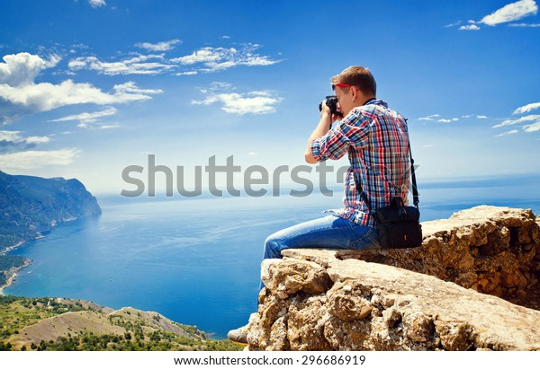 Photographer sits on top of a mountain and taking pictures