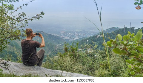 Photographer sitting on a edge of a mountain looking down over a valley in the himalayas on a cool summer afternoon.