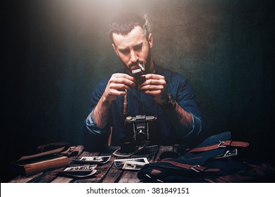 Photographer sorting vintage photos in dark room with vintage camera and accessories