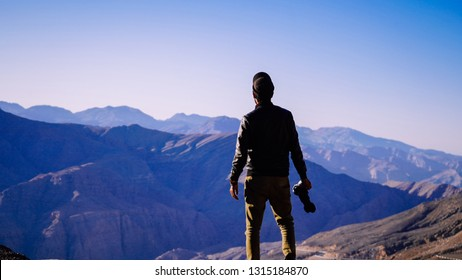 A photographer standing at the edge of the highest mountain of the UAE, Jebel Jais in Ras Al Khaimah with cold sunrise scenery in the background