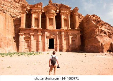 A photographer standing in front of the Monastery in Petra, Jordan