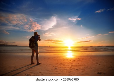 Photographer standing on beach  taking photo of beautiful sunset over sea