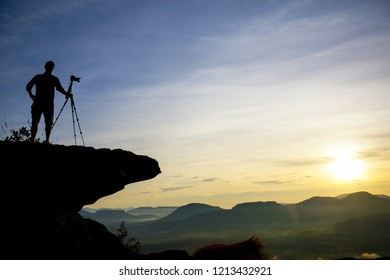 A photographer standing on a cliff, taking a photo of a sunrise silhouette