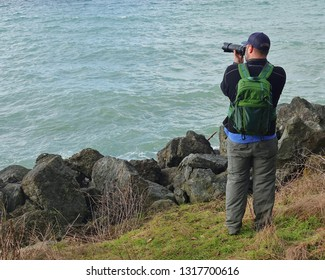 Photographer standing on grass along rocky shoreline of Puget Sound in Seattle WA taking a photo with long lens. The man is looking out over the water which is seen. The subject of his photo not seen.
