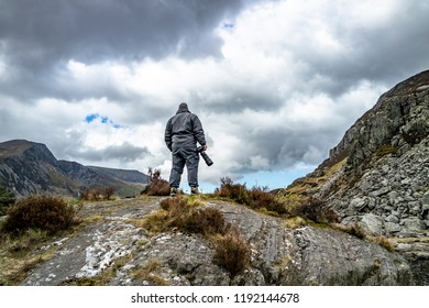 Photographer standing on mountain observing the dramatic sky.