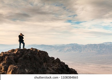 Photographer standing on a rock during sunrise at Dantes View, CA, USA