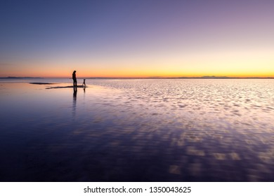 Photographer standing on the shallow water at dawn, Bonneville Salt Flats near Great Salt Lake, Utah