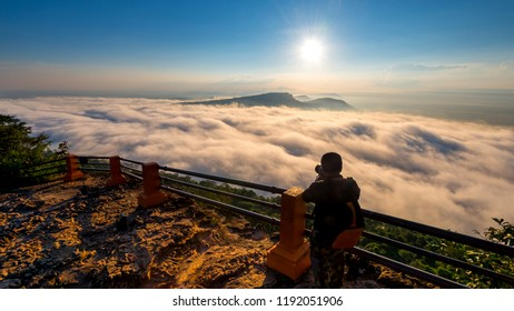 A photographer standing on top of Mountain at sunset with Mist.Asian male backpack in nature during sunset Relax time on holiday concept travel at Pha mor i dang,Sisaket province,Thailand,ASIA.