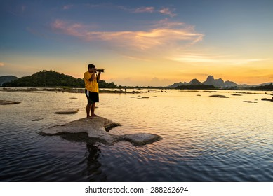 Photographer take a picture of beautiful sunset in lake