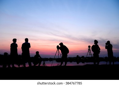 photographer take a picture on sunset background