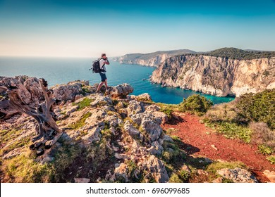 Photographer take picture on the top of cliff over the Ionian Sea. Sunny morning seascape of Zakynthos (Zante) island, Greece, Europe. Beauty of nature concept background.