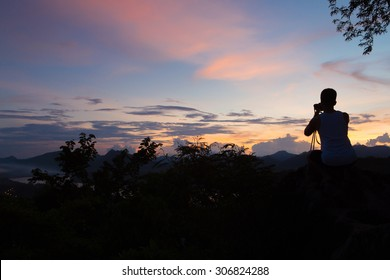 Photographer take a picture sunset at high mountain Pusi in Luang Prabang  . Silhouette picture style