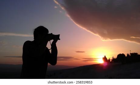 a photographer take a shot at the sun
