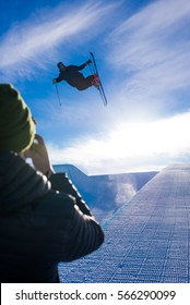 Photographer takes photo of halfpipe skier doing a trick