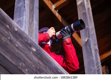 The photographer takes a photo with a telephoto lens