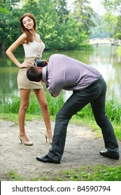 Photographer takes photo of young beautiful brunette woman wearing beige dress at summer green park.