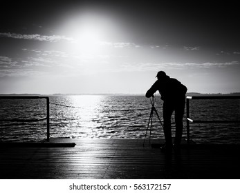Photographer takes photos with mirror camera and tripod at end of pier board. Fall foggy misty sunrise above smooth sea.