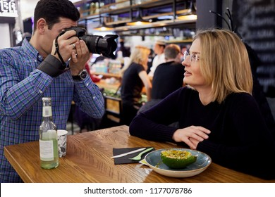 Photographer takes picture of woman sitting at table in cafe.