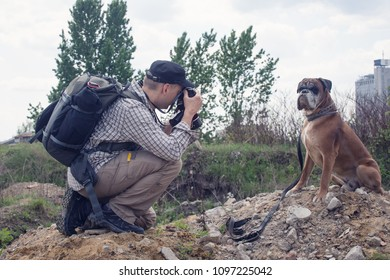 Photographer takes pictures of boxer dog.