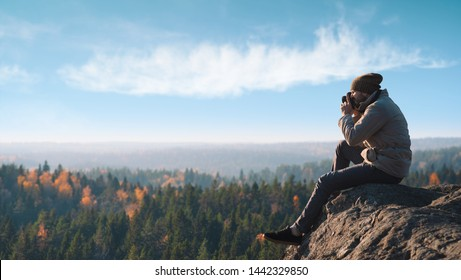 A photographer takes pictures of the landscape. He sits on a stone hill