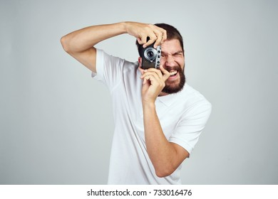 photographer takes pictures on the camera on a light background
