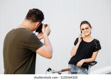 Photographer taking photo of cheerful girl talking on mobile phone. Behind the scenes of photoshoot