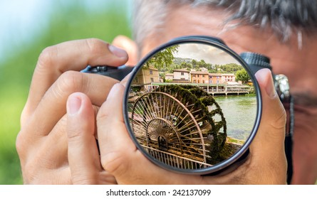 Photographer taking photo with DSLR camera at landscape in Provence. Shallow DOF
