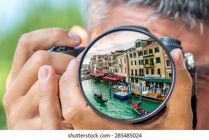 Photographer taking photo with DSLR camera at Venice Grand Canal. Shallow DOF