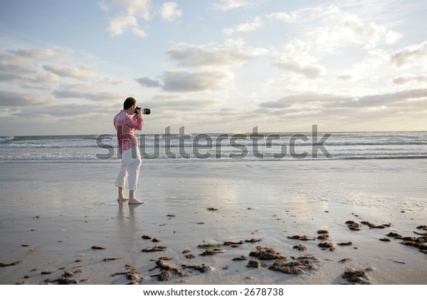 A photographer taking a photo on the beach.