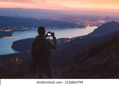 photographer taking photo on dslr camera at night after sunset twilights, city panoramic mountain landscape low light, dusk