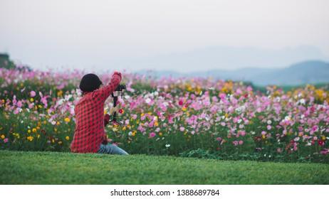 photographer taking photo and video of flowers mountain, landscape