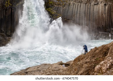 Photographer taking photo of waterfall in Island. Focus on a photographer.