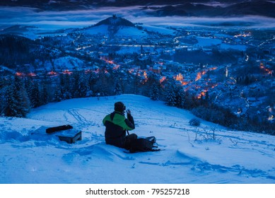Photographer taking a photo of winter nature above beautiful winter city. Magic fairy tale scenery.. Banska Stiavnica, Slovakia.