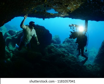 photographer taking photos underwater of a civil man model