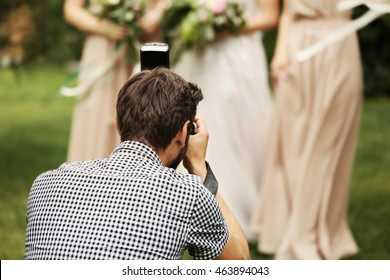 Photographer taking picture of bride with bridesmaids