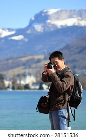 photographer taking picture in front of snow mountain