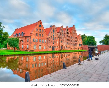 Photographer taking picture of Group Beautiful historic houses on river bank in Lubeck. Germany
