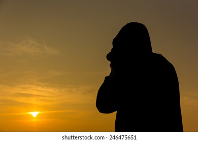 photographer taking picture of landscape during sunrise.