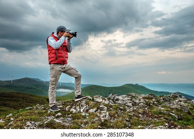 Photographer is taking a picture of  landscape in mountains