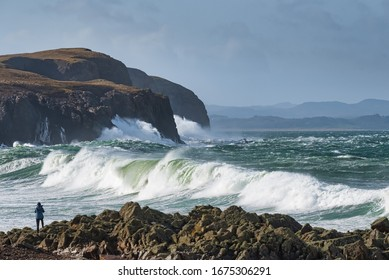 Photographer taking picture of large waves coming in from the Atlantic ocean on the rocky shore at Dunaff County Donegal Ireland