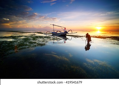 Photographer is taking a picture of sunrise with traditional fishing boats at Sanur Beach Bali Indonesia.