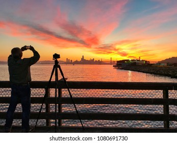 Photographer is taking a picture of sunset with San Francisco city silhouette, California, USA