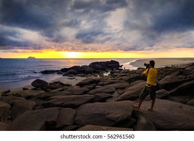Photographer is taking a picture of sunsun on the rock at beach with amazing sky and Cloud