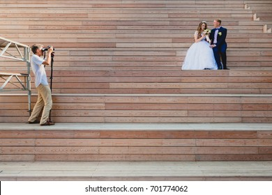 Photographer taking Pictures of the Bride and Groom at wooden steps