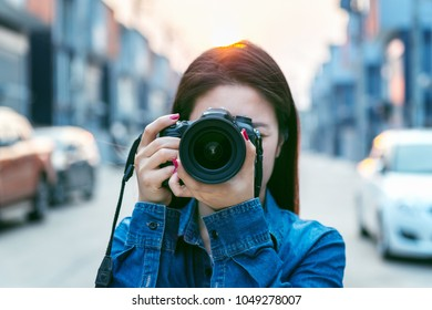 Photographer taking pictures with digital camera. Vintage tone.