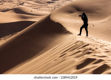 Photographer taking pictures of dunes in Desert Sahara with beautiful lines and colors at sunrise. Merzouga, Morocco