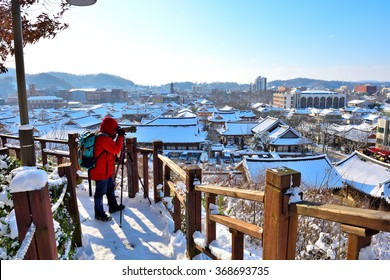 Photographer taking pictures at Jeonju traditional Korean village covered with snow, South Korea.2016-january-24