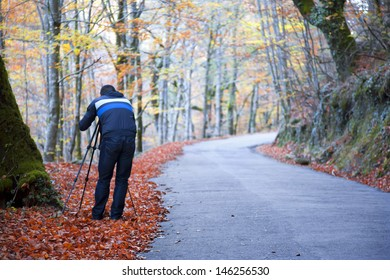 Photographer taking pictures outdoors during the Autumn season