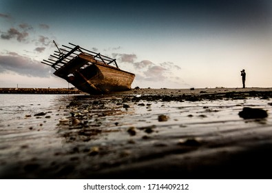 photographer taking a shot of Dhow boat wreck, nice wide shot to be used in a double spread page